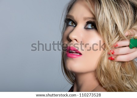 portrait of a beautiful young woman with curly blond hair and glamour make-up with pink lips wearing a fashion green ring on red manicure hands
