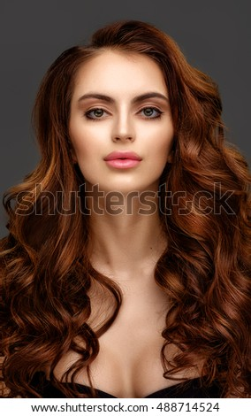 Portrait of a beautiful young woman with elegant long red shiny hair. Redhead girl.