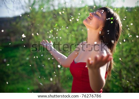 portrait of a beautiful young woman with flower outdoor - stock photo