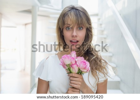 Portrait of a beautiful young woman with flowers standing on stairs at home