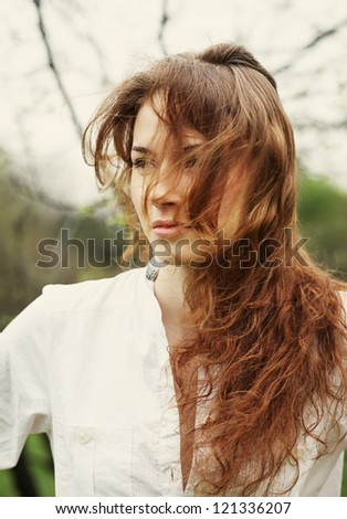 Portrait of a beautiful young woman with flying hair