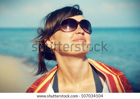 portrait of a beautiful young woman with glasses in the background of the sea - stock photo