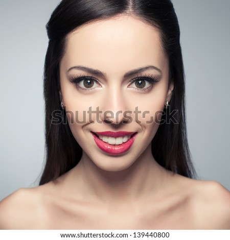 Portrait of a beautiful young woman with great white shiny smile posing over light-gray background. Healthy skin. Studio shot - stock photo