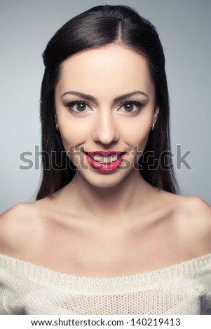 Portrait of a beautiful young woman with great white shiny smile posing over light-gray background. Healthy skin. Studio shot