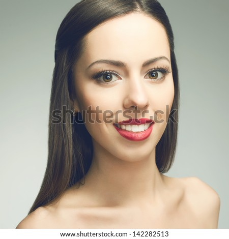 Portrait of a beautiful young woman with great white shiny smile posing over light-gray background. Healthy skin and teeth. Close up. Studio shot
