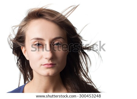 Portrait of a beautiful young woman with hair flying isolated on white with copy-space