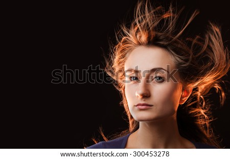 Portrait of a beautiful young woman with hair flying on dark background with copy-space