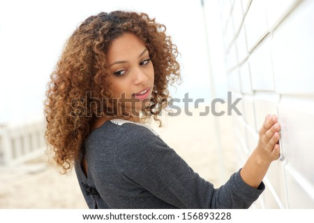 Portrait of a beautiful young woman with hand on wall and looking over shoulder
