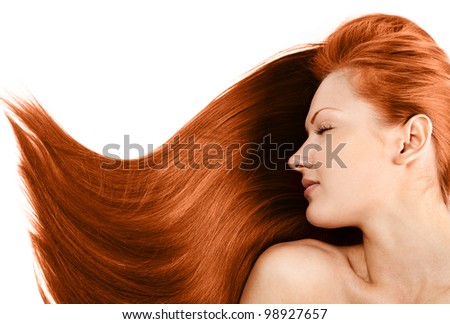 portrait of a beautiful young woman with healthy long red hair