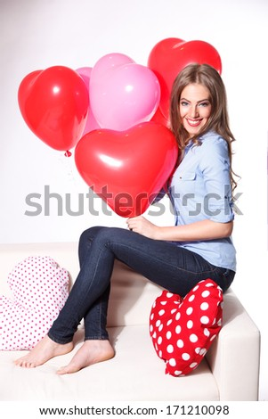 Portrait of a beautiful young woman with heart shaped balloons a - stock photo