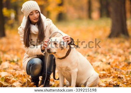 Portrait of a beautiful young woman with her dog while walking in the autumn park - stock photo