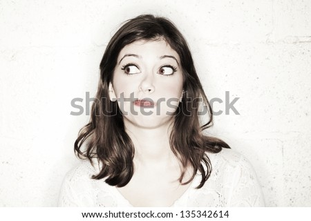Portrait of a beautiful young woman with her eyes wide open, glancing sideways, she's looking completely clueless in the cutest manner possible. - stock photo