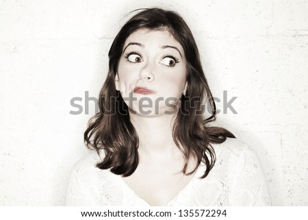 Portrait of a beautiful young woman with her eyes wide open, glancing sideways, she's looking completely shocked in the cutest manner possible. - stock photo