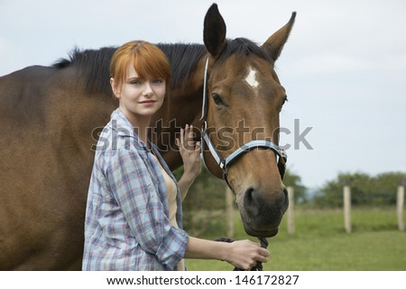 Portrait of a beautiful young woman with horse in field