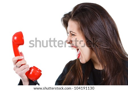 Portrait of a beautiful young woman with long brown hair, screaming into a red retro telephone receiver - isolated on white - stock photo