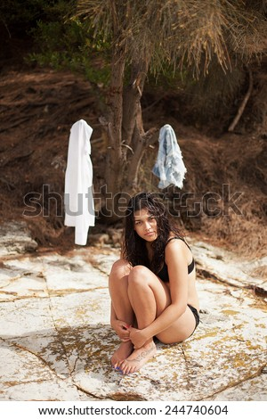 Portrait of a beautiful young woman with long brunette hair drying herself in the sun after her clothes got wet - stock photo