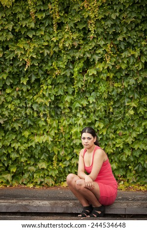 Portrait of a beautiful young woman with long brunette hair sitting on kerb - stock photo