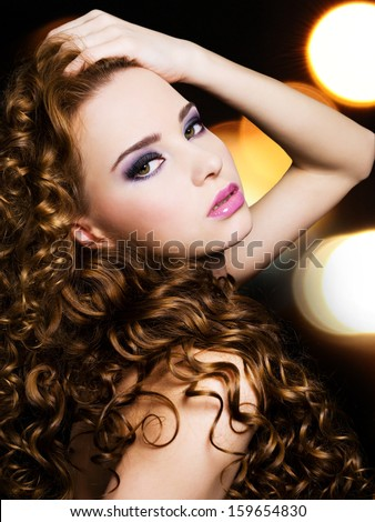 Portrait of a beautiful young woman with  long curly hairs over bright night lights
