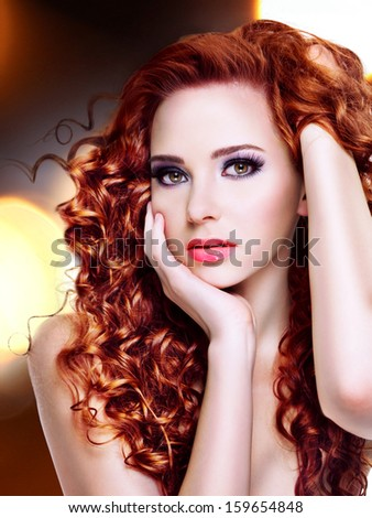 Portrait of a beautiful young woman with  long curly hairs over bright night lights - stock photo