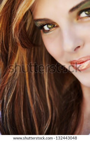 Portrait of a beautiful young woman with long hair wearing fashion makeup - stock photo