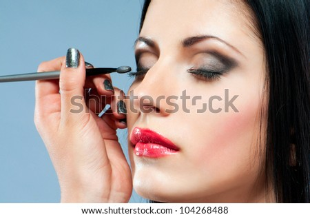 portrait of a beautiful young woman with make-up brush
