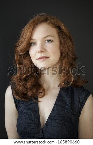 Portrait of a beautiful young woman with red hair and blue eyes. - stock photo