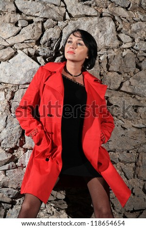 portrait of a beautiful young woman with red jacket - stock photo