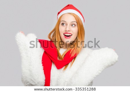 Portrait of a beautiful young woman with red Santa hat looking to the side surprised with hands up. Happy girl dressed for Christmas time. Merry Christmas. - stock photo