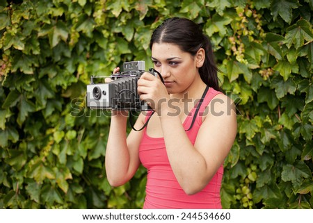 Portrait of a beautiful young woman with retro old camera - stock photo