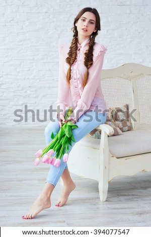 Portrait of a beautiful young woman with spring bouquet of pink tulips