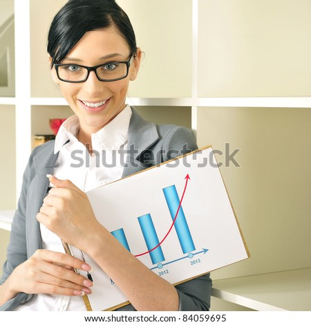 Portrait of a beautiful young woman with statistics. Office background. - stock photo
