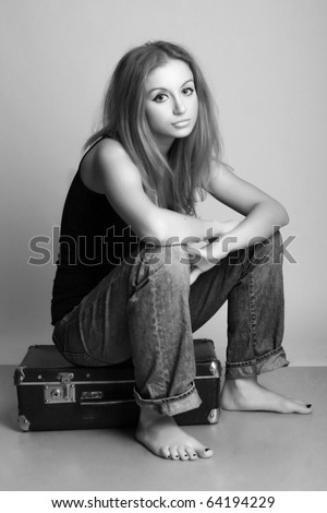 portrait of a beautiful young woman with suitcase (black and white photography) - stock photo