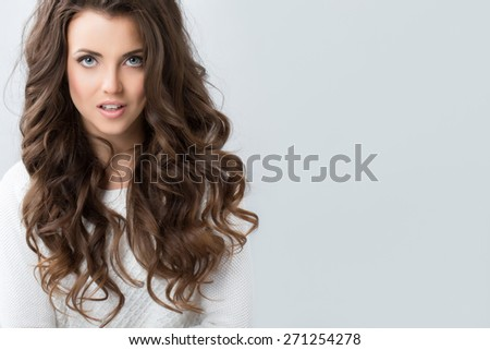 Portrait of a beautiful young woman with wavy hair. Hair and makeup. - stock photo