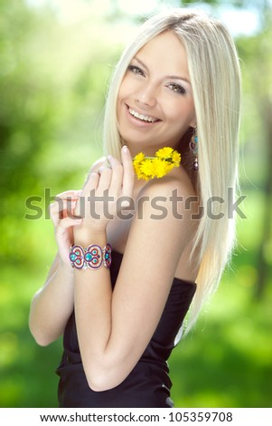 Portrait of a beautiful young woman with yellow flowers - stock photo