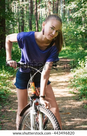 Portrait of a beautiful young women with a bicycle on park background. Sexy woman with bike in a country road - stock photo