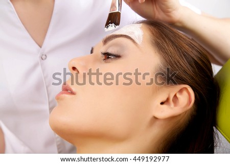 Portrait of a beauty attractive young woman getting beauty skin mask treatment on her face with brush