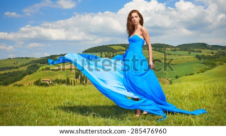 Portrait of a beauty woman in blue dress on Italy hills - stock photo