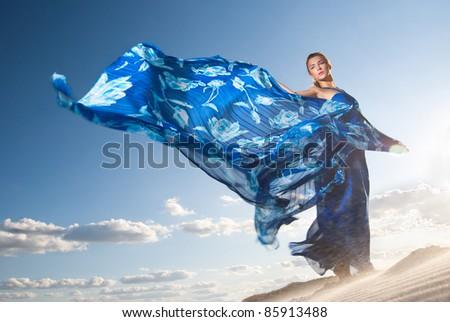 Portrait of a beauty woman in blue dress on the desert - stock photo