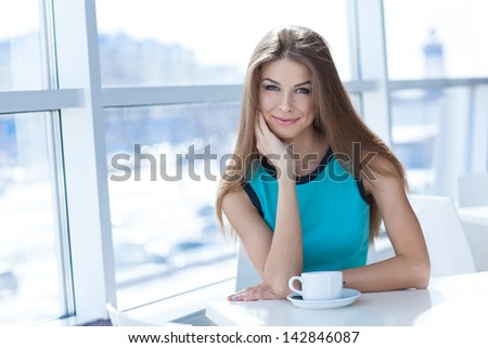 Portrait of a beauty young woman with a tea cup sitting in a coffe shop
