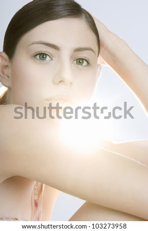 Portrait of a beauty young woman with direct back light on a white background. - stock photo