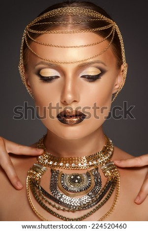 Portrait of a beautyful woman with golden makeup wearing jewelry, Egyptian Style Woman