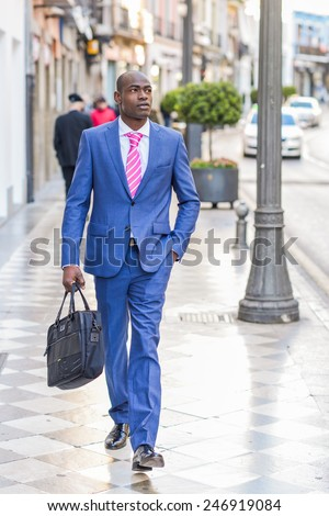 Portrait of a black business man walking on the street with a modern briefcase - stock photo