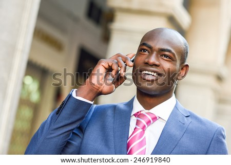 Portrait of a black businessman wearing suit talking with his smartphone in urban background - stock photo