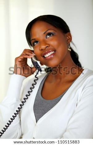 Portrait of a black woman looking up while talking on phone at soft colors composition