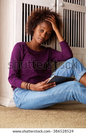 Portrait of a black woman sitting with digital tablet