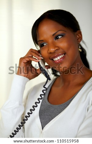 Portrait of a black woman smiling and speaking on phone at soft colors composition