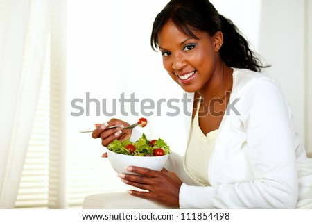 Portrait of a black young woman smiling and eating a green salad and looking at you. - stock photo