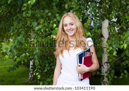 Portrait of a blond girl with books - stock photo