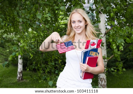 Portrait of a blond girl with USA and Canadian flags - stock photo