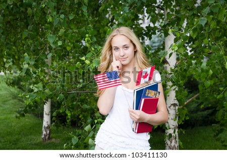 Portrait of a blond girl with USA and Canadian flags and books - stock photo